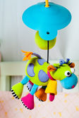 Colorful turning cow baby toy over the bed — Stock Photo