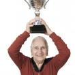 Isolated old lady raising trophy on white background - Stock Photo