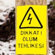 Turkish electricity hazard plate on wood pillar — Stock Photo