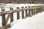 Wooden baluster of the bridge over the frozen lake — Stock Photo