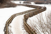 Curly wooden bridge over the frozen lake — Stock Photo
