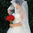 Bride holding red roses bouquet and bridal veil in hand side shot — Stok fotoğraf