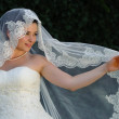 Bride holding open her bridal veil with her finger — Photo