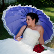 Bride holding umbrella and red roses boquet in hand — Stock fotografie