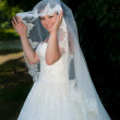 Brite holding open her bridal veil with two hands — Foto de Stock