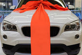 Brand new white present car with large red ribbon decoration — Stock Photo