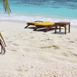 Stock Photo: Beach chairs in white sand in front of blue ocean