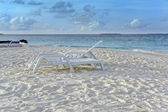 Leżaki w białym piaskiem przed niebieski ocean — Zdjęcie stockowe