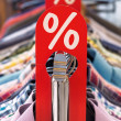 Fashion sale rack with red label shirts and hangers — Stock Photo #48188511