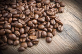 Coffee beans on wood table — Stock Photo
