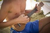 Boy playing the ukulele — Stock fotografie