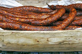 Romanian sausage in a rustic wooden bowl carved — Stock Photo