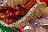 Sausages in wicker basket and bacon — Stock Photo