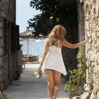 Beautiful woman walking barefoot in the street by the sea — Stock Photo #13174424