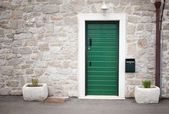 Green door in old stone house — Stock Photo
