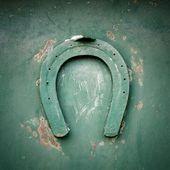 Lucky horseshoe on green metal — Stock Photo