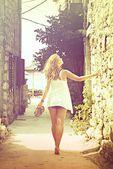 Beautiful woman walking barefoot in the street, cross process — Stock Photo