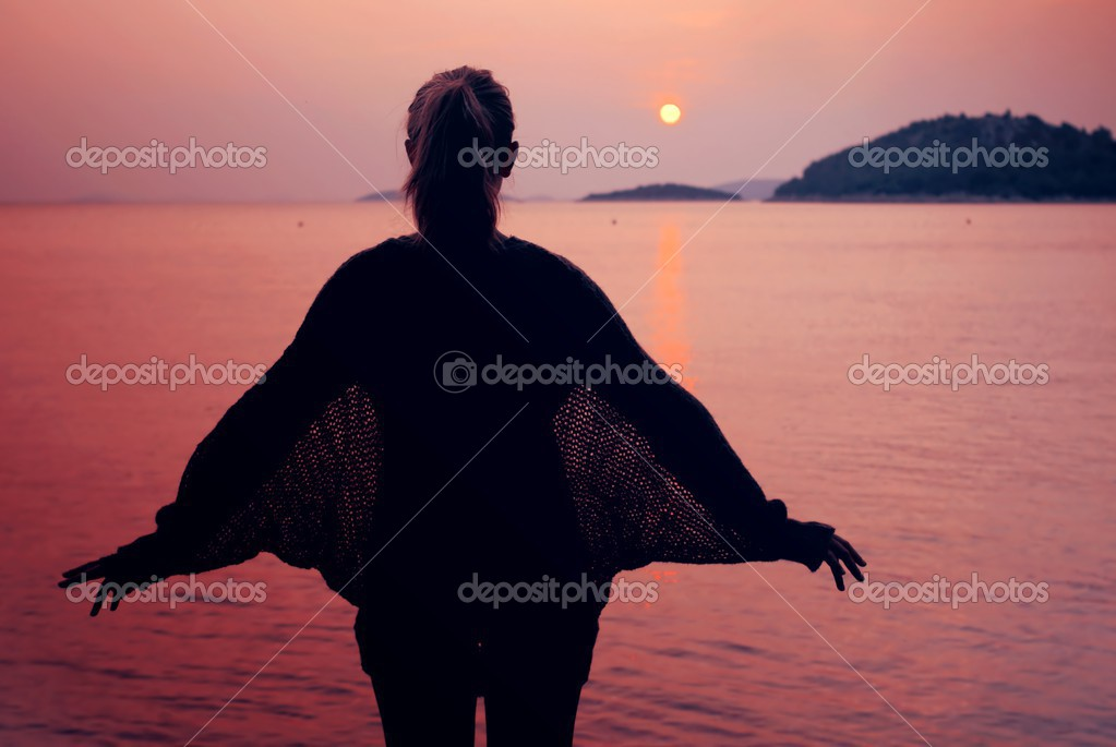 Silhouette of a young woman spreads her hands at the sea with sunset — Stock Photo #13359153