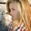 Stock Photo: Portrait of attractive young woman posing in front of stone wall