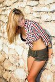 Giovane donna in posa davanti al muro di pietra — Foto Stock