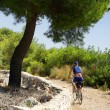 Senior cyclist riding gravel road by sea, Croatia — Stock Photo