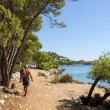 Stock Photo: Tourists walking along the coast road by sea, Croatia Dalmatia
