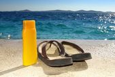 Suntan cream or oil and sandals on beach — Stock Photo