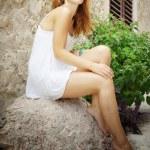 Woman sitting barefoot on street — Stock Photo #14084756