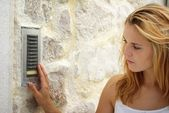 Woman using house intercom, outdoor — Stock Photo