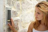 Woman using house intercom, outdoor — Stock Photo