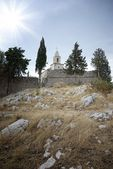 Old small church and stone walls, hill — Stock Photo