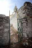 Open gate in old stone wall, church in background — Stock Photo