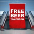 Free beer advertising flag and escalator — Stock Photo