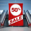 50 percent sale advertising flag and escalator — Stock Photo