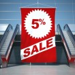 5 percent sale advertising flag and escalator — Stock Photo