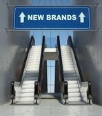 Moving escalator stairs in mall, new brands sign — Zdjęcie stockowe