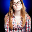 Sad young girl with nerd glasses and open exercise book - Stockfoto