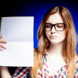 Disappointed young girl with nerd glasses holding open exercise book — Stock Photo #22473963