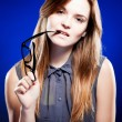 Young woman biting a nerd glasses with interested look - Stock Photo