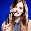 Young woman biting a nerd glasses with interested look — Stock fotografie
