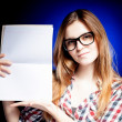 Happy young girl with nerd glasses holding exercise book — Stock Photo