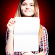 Smiling and proud young girl holding exercise book - Stock Photo
