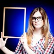 Woman with nerd glasses holding wooden frame - ストック写真