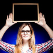 Woman with nerd glasses holding wooden frame over her head - Stock Photo