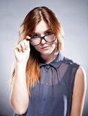 Strict serious young woman holding nerd glasses — Stock Photo
