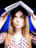 Confused and puzzled young girl holding exercise book on her head — Stock Photo