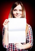 Smiling and proud young girl holding exercise book — Stock Photo