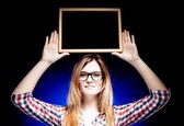 Woman with nerd glasses holding wooden frame over her head — Stock Photo