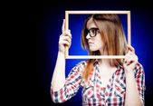 Woman with nerd glasses looking left, frame around her face — Stock Photo