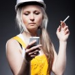 Young architect woman construction worker, cigarette and phone - Stock Photo